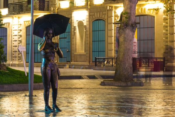 One of many cool statues. Girl with phone and umbrella
