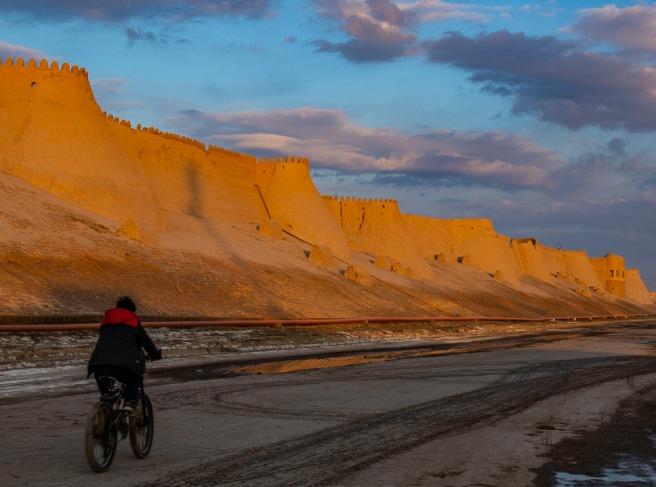 Boy biking along the city wall in Khiva