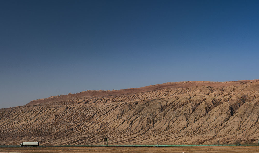 A truck passes the Flaming Mountains in Xinjiang provins